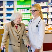 Senior woman and doctor laughing in pharmacy.